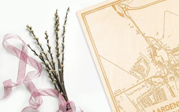 Hier ligt de houten plattegrond Aardenburg naast een bloemetje als gepersonaliseerd cadeau voor haar.
