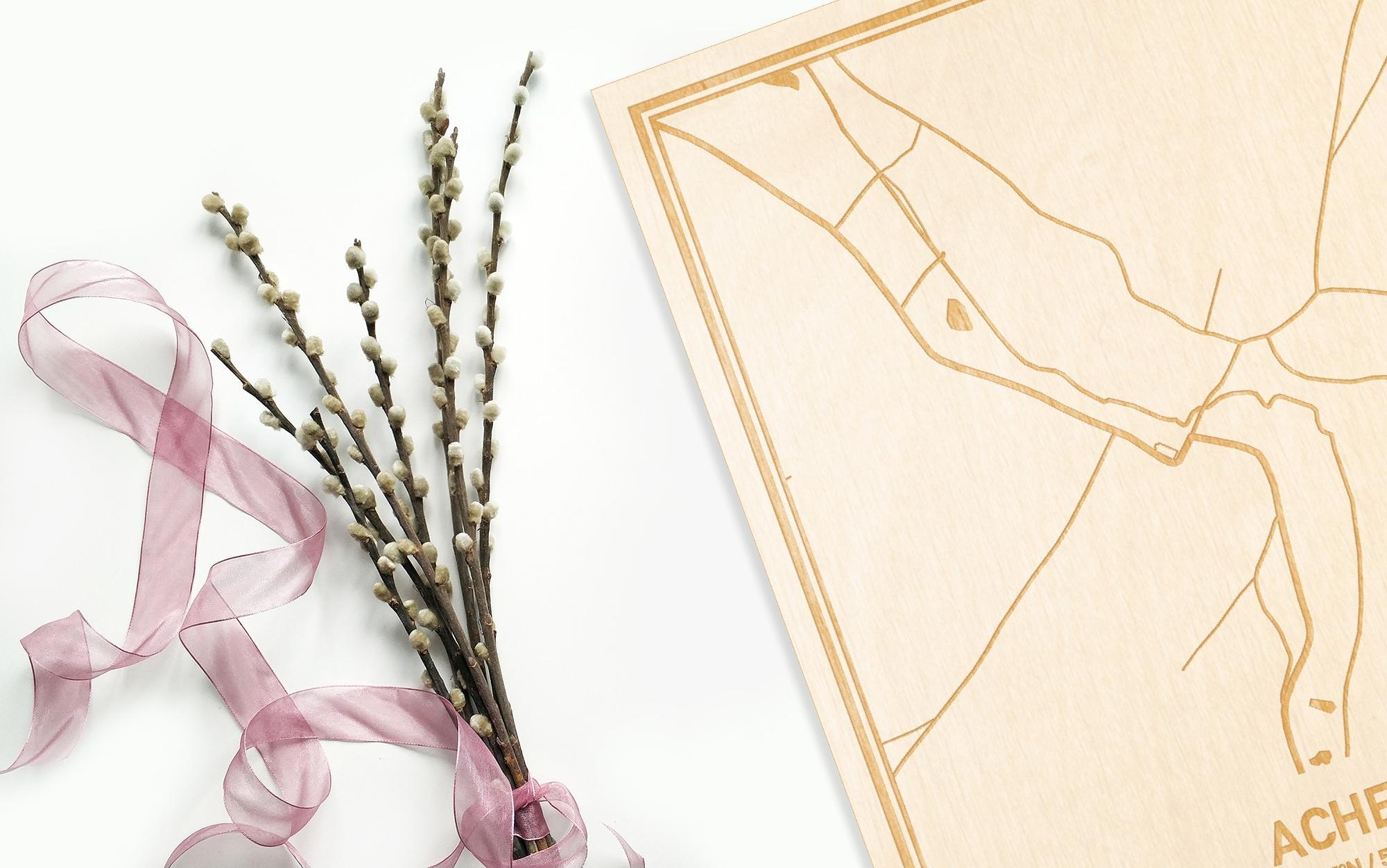 Hier ligt de houten plattegrond Achet naast een bloemetje als gepersonaliseerd cadeau voor haar.