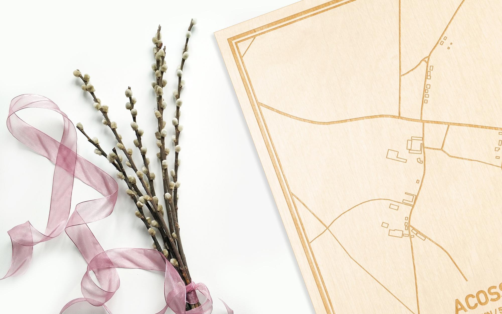 Hier ligt de houten plattegrond Acosse naast een bloemetje als gepersonaliseerd cadeau voor haar.