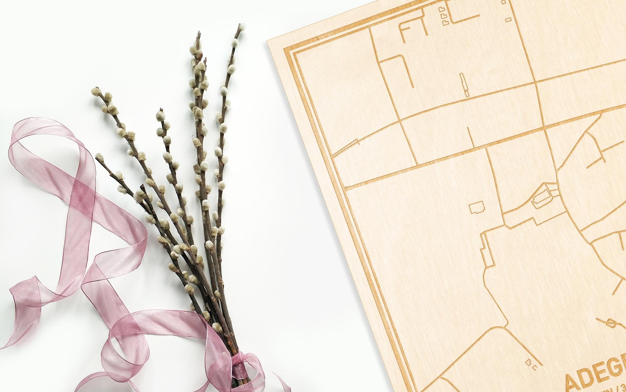 Hier ligt de houten plattegrond Adegem naast een bloemetje als gepersonaliseerd cadeau voor haar.