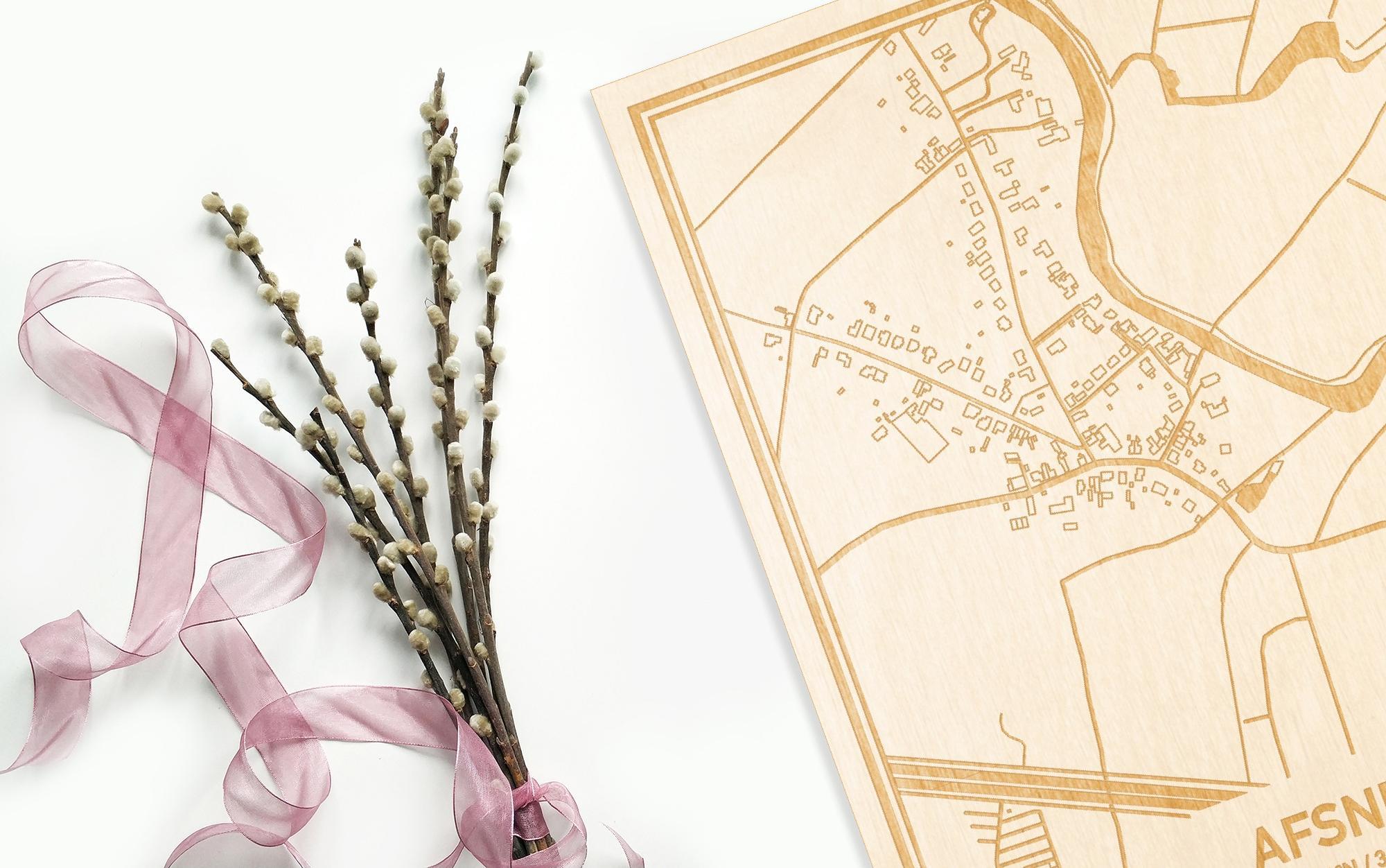 Hier ligt de houten plattegrond Afsnee naast een bloemetje als gepersonaliseerd cadeau voor haar.