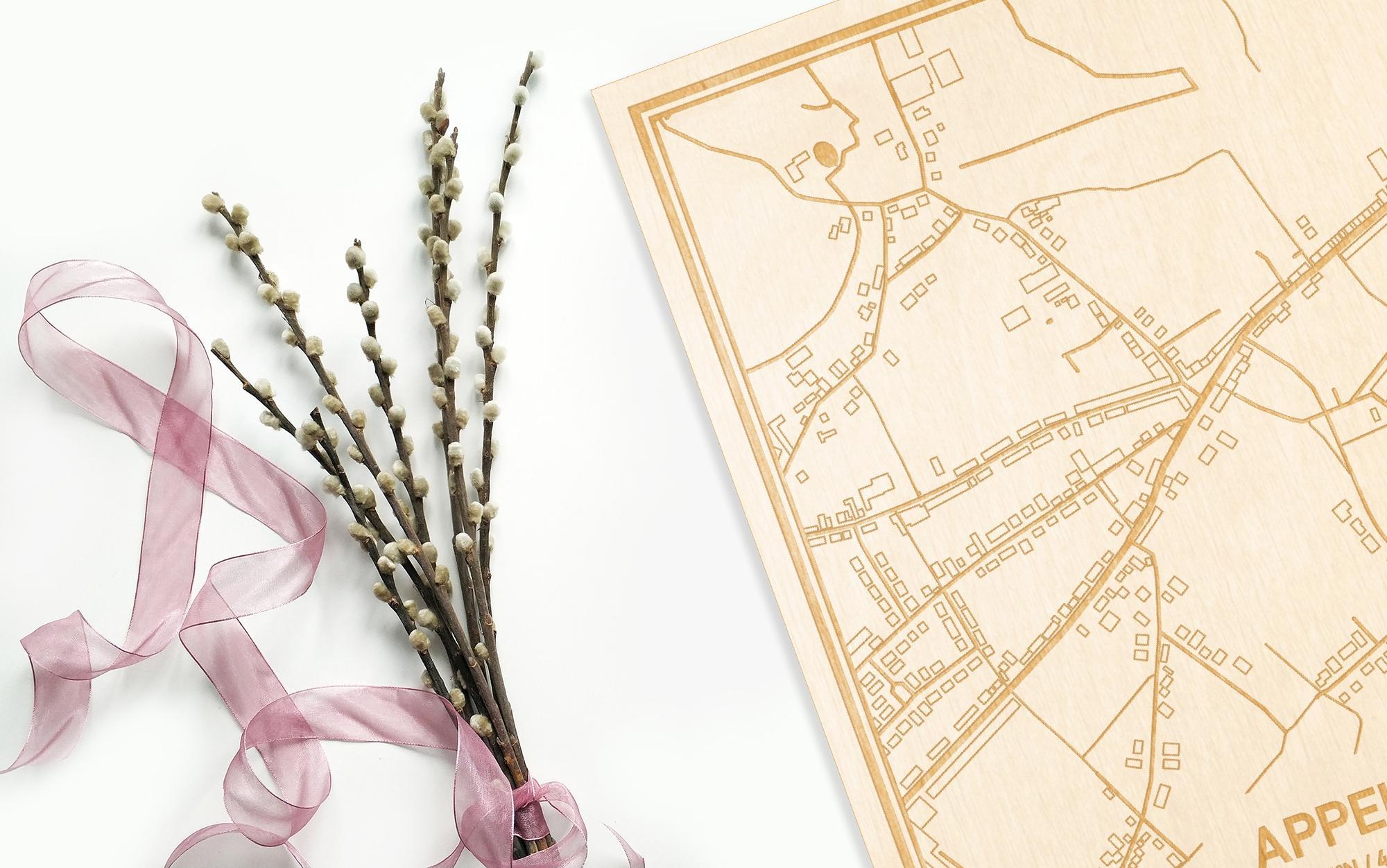 Hier ligt de houten plattegrond Appels naast een bloemetje als gepersonaliseerd cadeau voor haar.