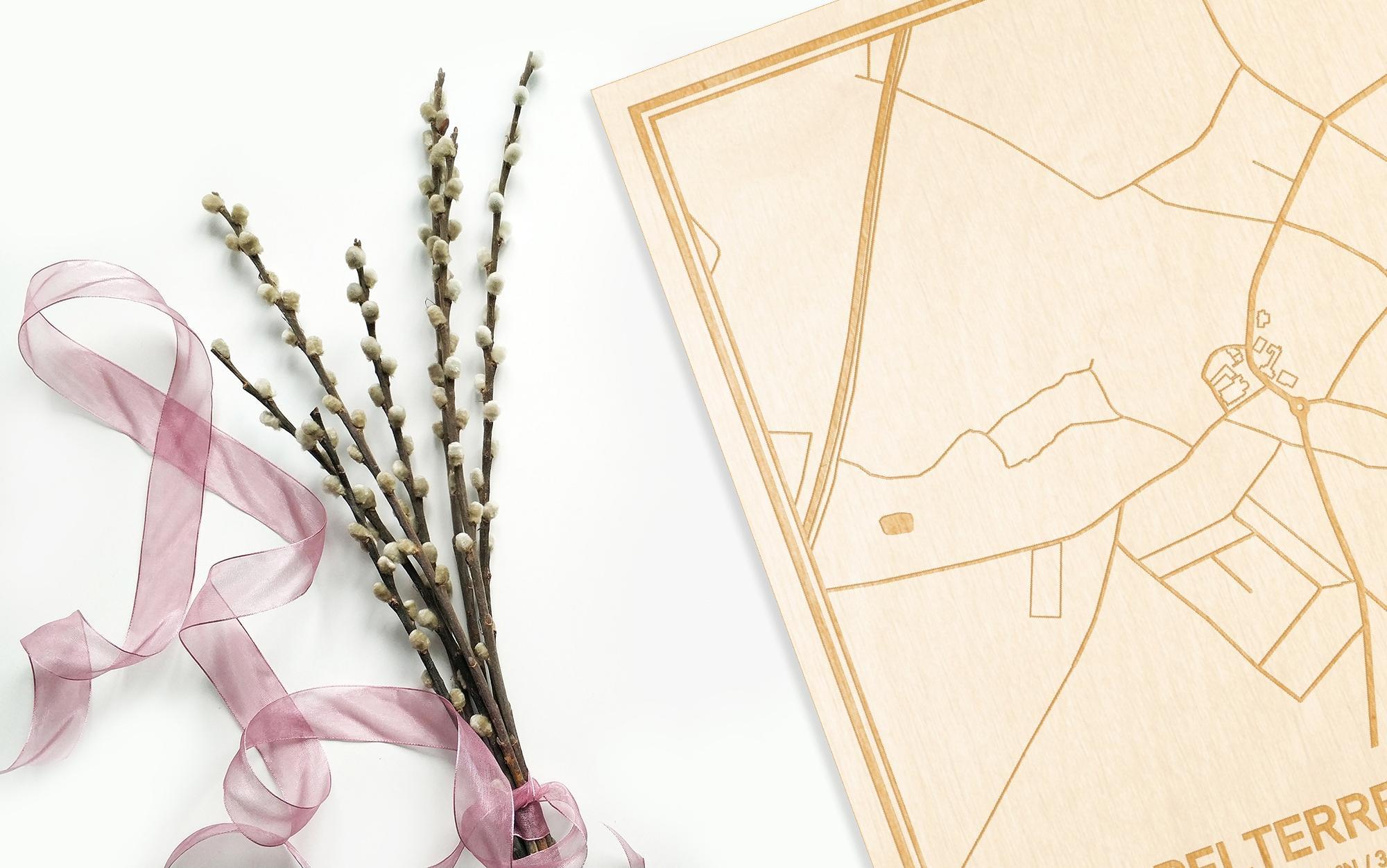 Hier ligt de houten plattegrond Appelterre-Eichem naast een bloemetje als gepersonaliseerd cadeau voor haar.