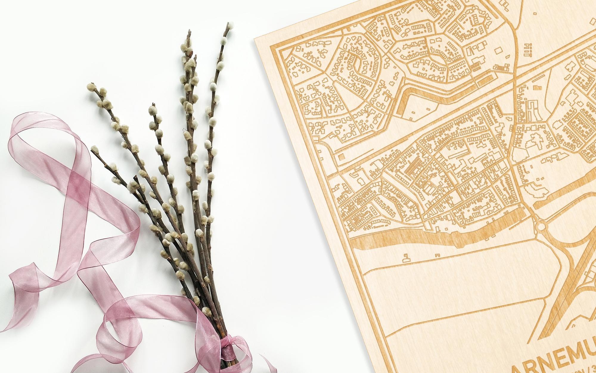 Hier ligt de houten plattegrond Arnemuiden naast een bloemetje als gepersonaliseerd cadeau voor haar.