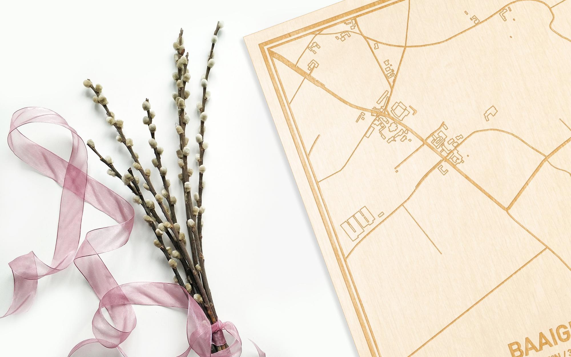 Hier ligt de houten plattegrond Baaigem naast een bloemetje als gepersonaliseerd cadeau voor haar.
