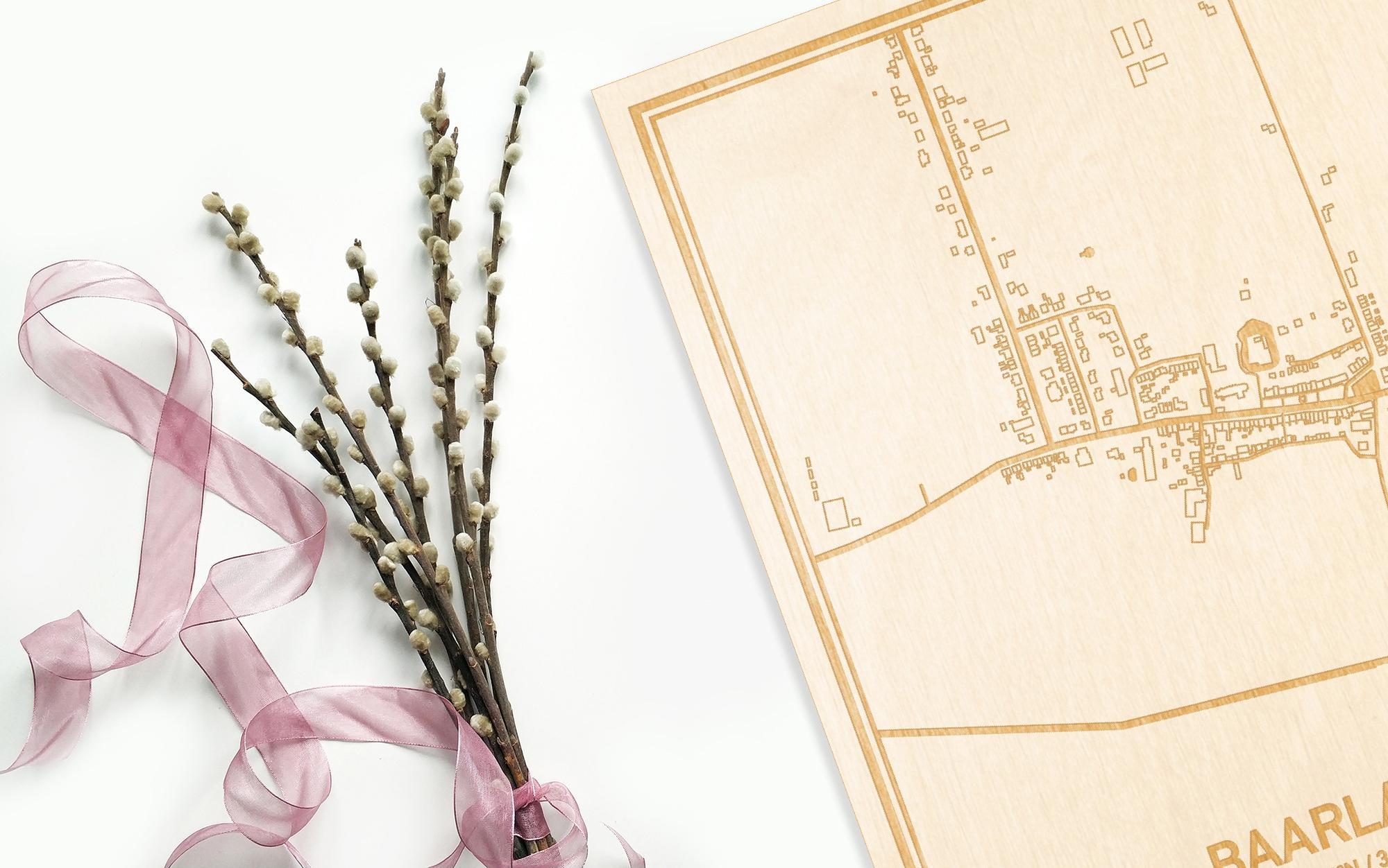 Hier ligt de houten plattegrond Baarland naast een bloemetje als gepersonaliseerd cadeau voor haar.
