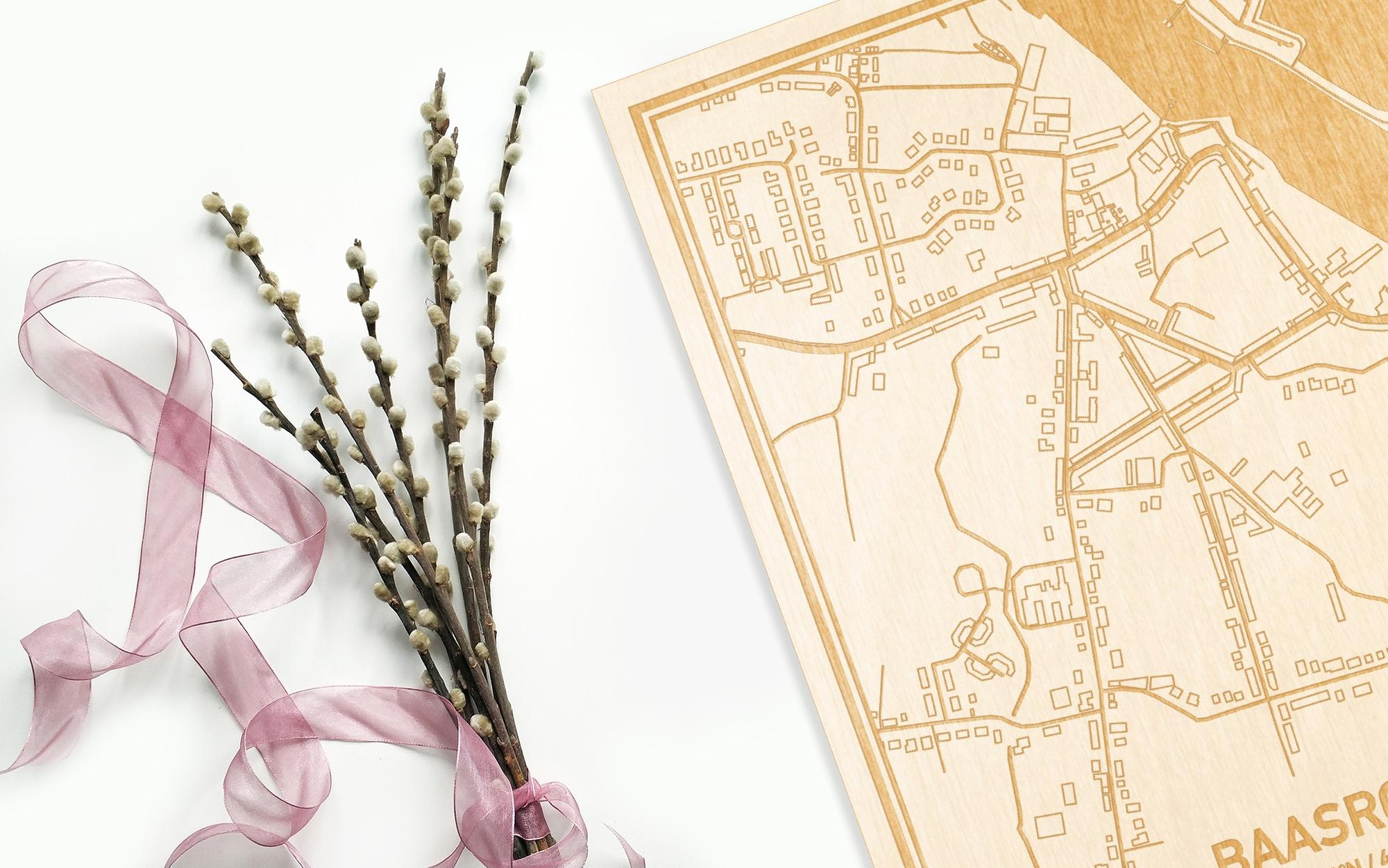 Hier ligt de houten plattegrond Baasrode naast een bloemetje als gepersonaliseerd cadeau voor haar.