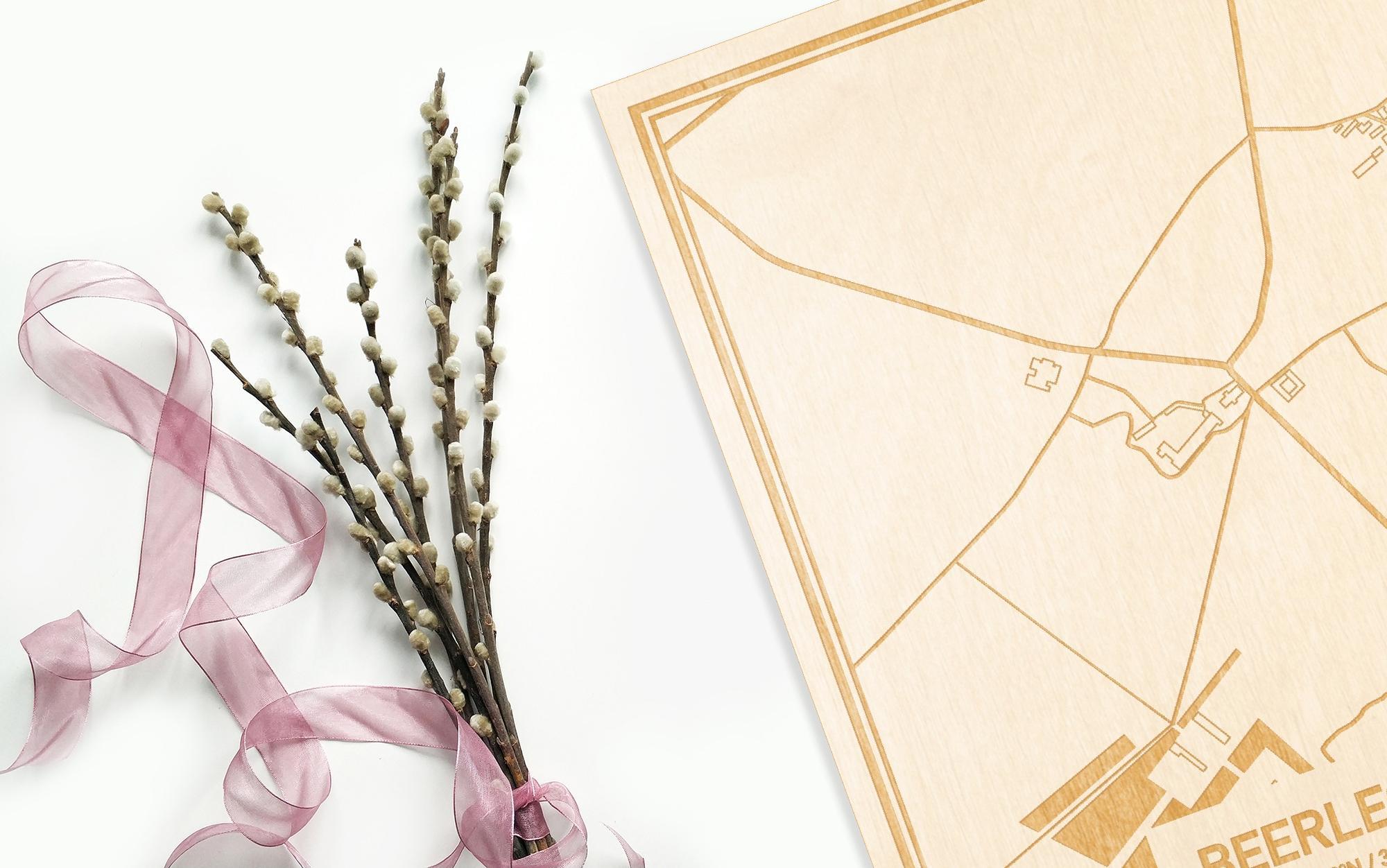 Hier ligt de houten plattegrond Beerlegem naast een bloemetje als gepersonaliseerd cadeau voor haar.