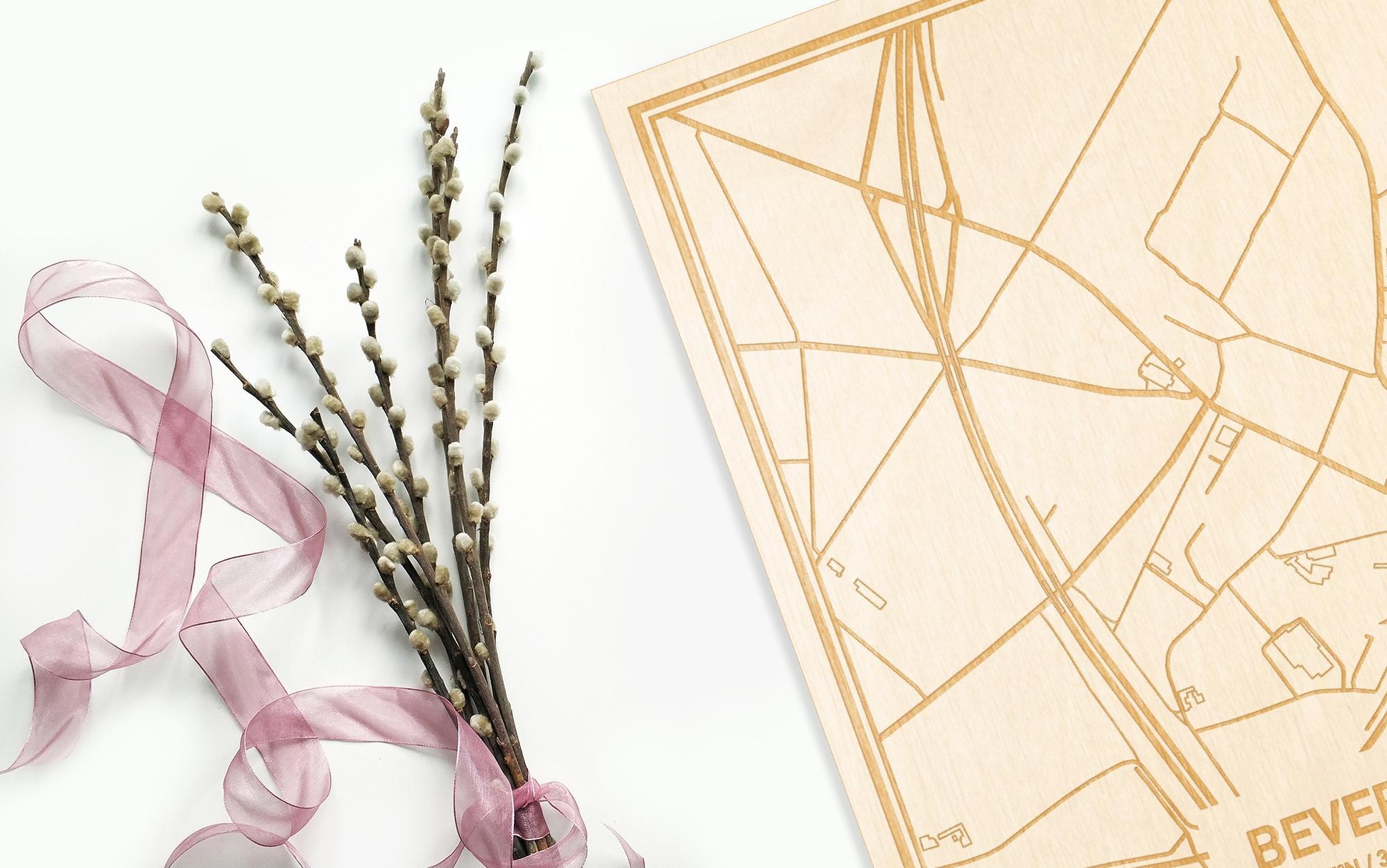 Hier ligt de houten plattegrond Bevere naast een bloemetje als gepersonaliseerd cadeau voor haar.