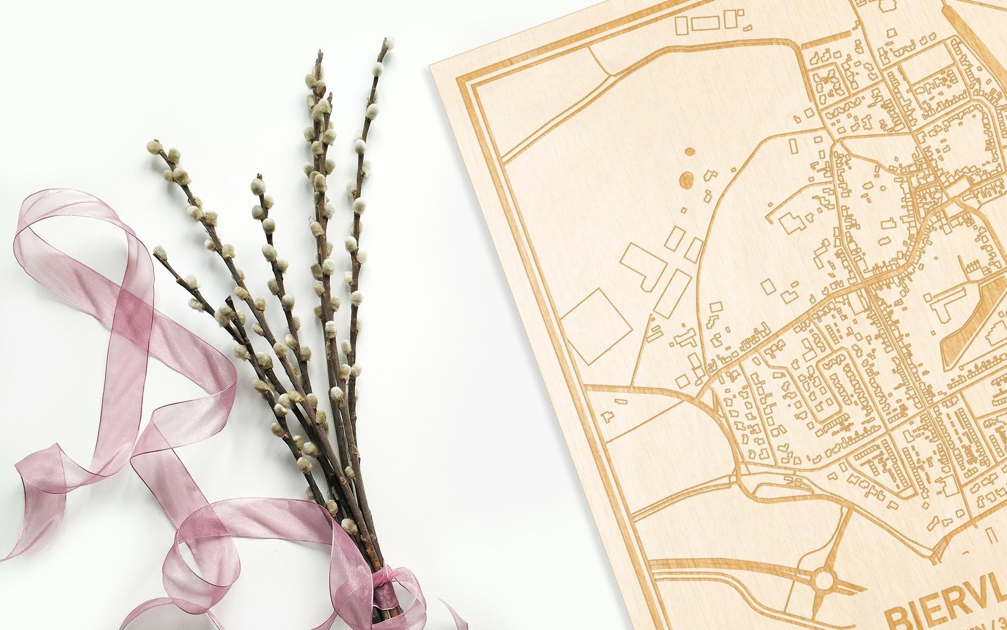 Hier ligt de houten plattegrond Biervliet naast een bloemetje als gepersonaliseerd cadeau voor haar.