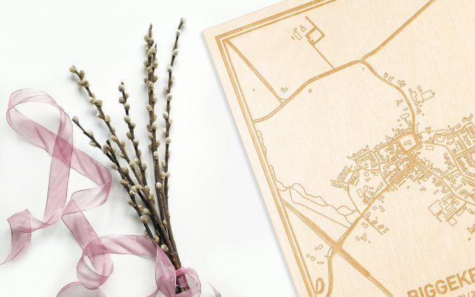 Hier ligt de houten plattegrond Biggekerke naast een bloemetje als gepersonaliseerd cadeau voor haar.