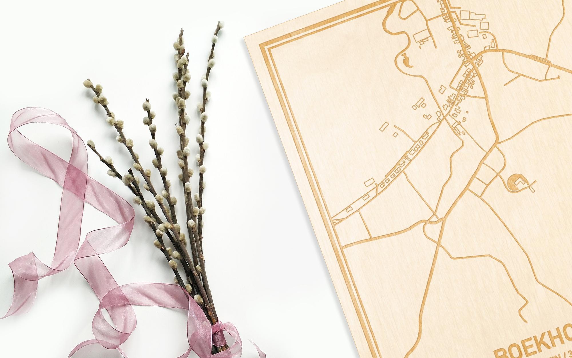 Hier ligt de houten plattegrond Boekhoute naast een bloemetje als gepersonaliseerd cadeau voor haar.