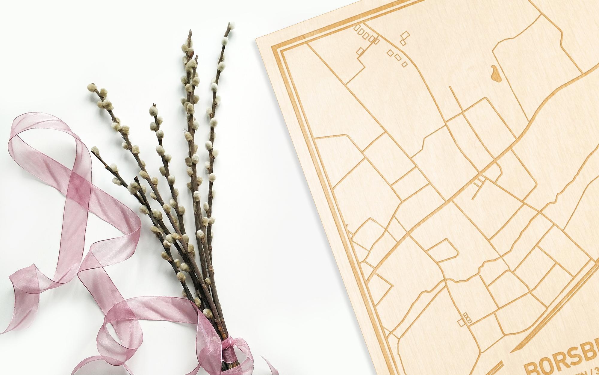 Hier ligt de houten plattegrond Borsbeke naast een bloemetje als gepersonaliseerd cadeau voor haar.