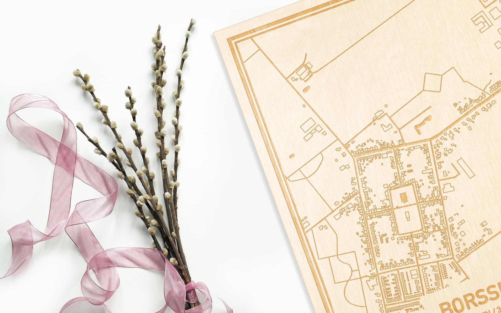 Hier ligt de houten plattegrond Borssele naast een bloemetje als gepersonaliseerd cadeau voor haar.