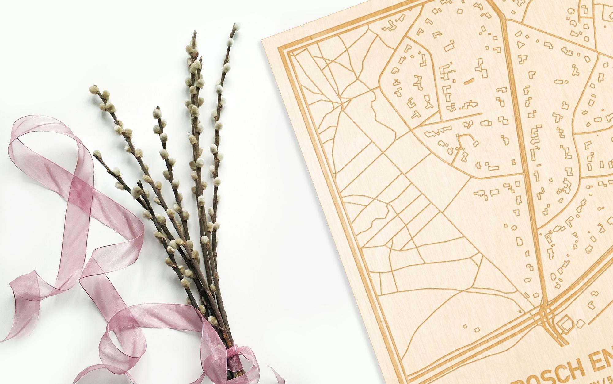 Hier ligt de houten plattegrond Bosch en Duin naast een bloemetje als gepersonaliseerd cadeau voor haar.