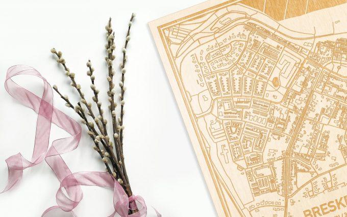 Hier ligt de houten plattegrond Breskens naast een bloemetje als gepersonaliseerd cadeau voor haar.