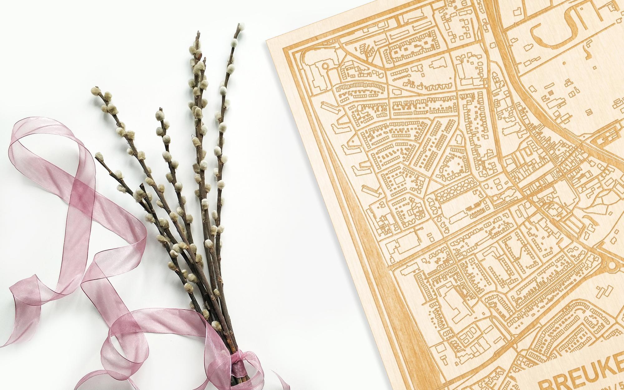Hier ligt de houten plattegrond Breukelen naast een bloemetje als gepersonaliseerd cadeau voor haar.