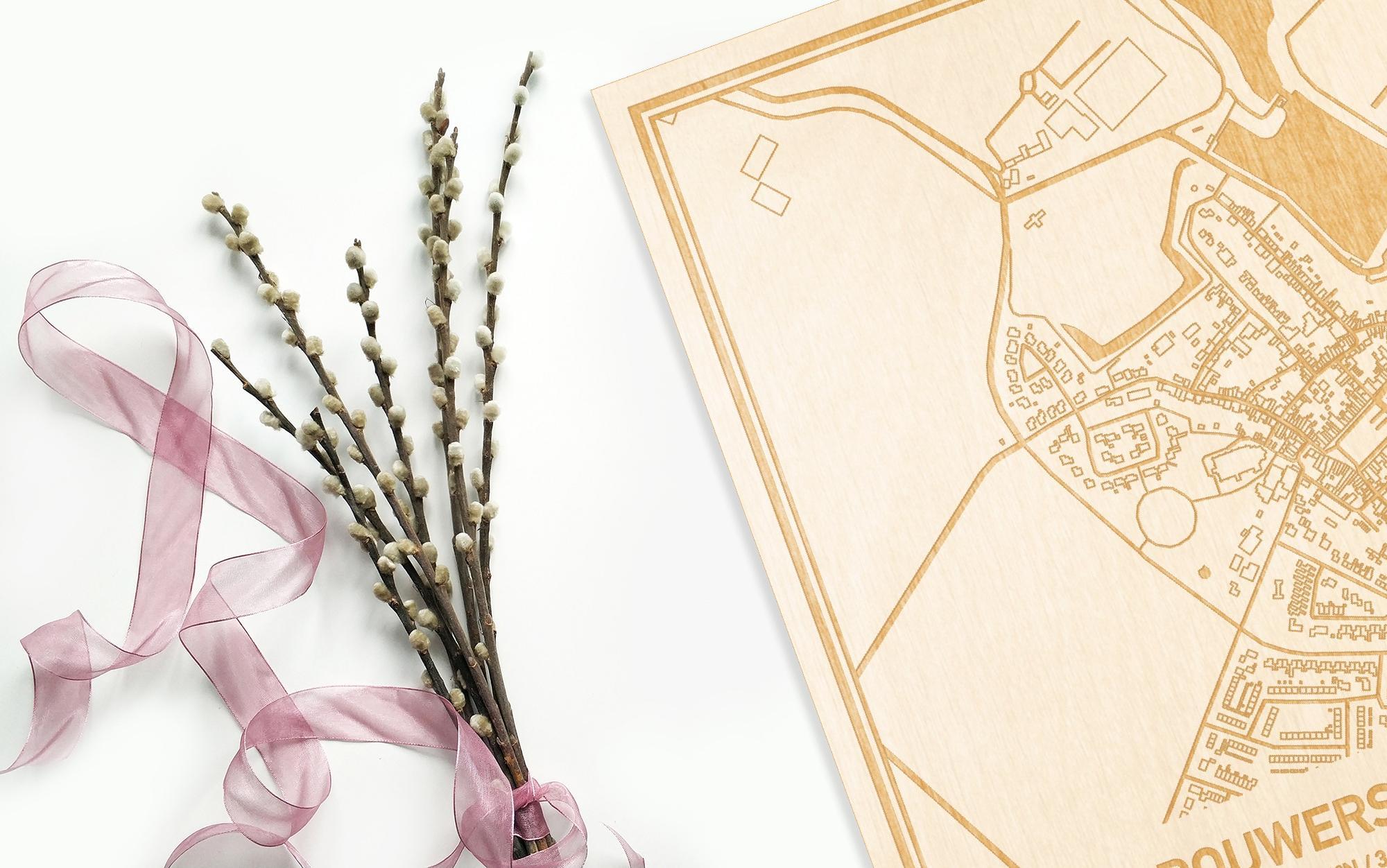 Hier ligt de houten plattegrond Brouwershaven naast een bloemetje als gepersonaliseerd cadeau voor haar.