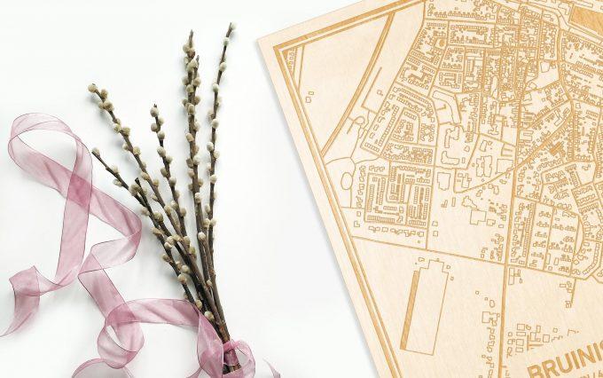 Hier ligt de houten plattegrond Bruinisse naast een bloemetje als gepersonaliseerd cadeau voor haar.