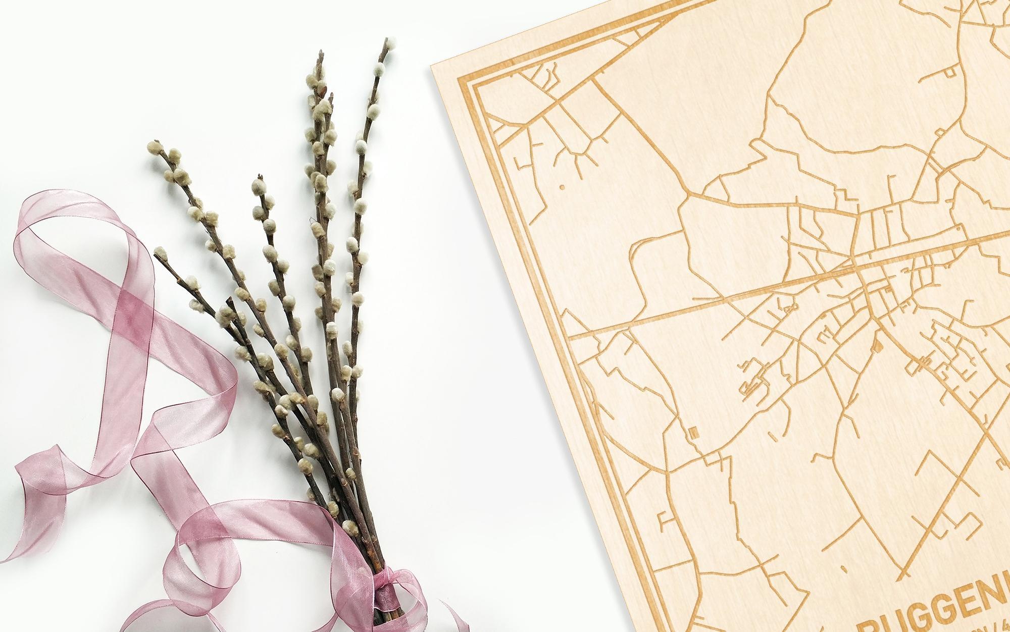Hier ligt de houten plattegrond Buggenhout naast een bloemetje als gepersonaliseerd cadeau voor haar.