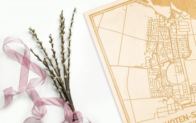 Hier ligt de houten plattegrond Bunschoten-Spakenburg naast een bloemetje als gepersonaliseerd cadeau voor haar.