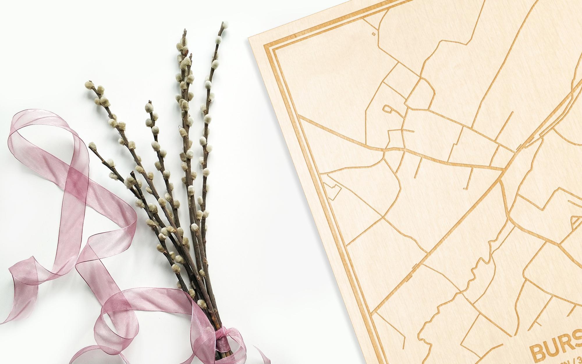 Hier ligt de houten plattegrond Burst naast een bloemetje als gepersonaliseerd cadeau voor haar.