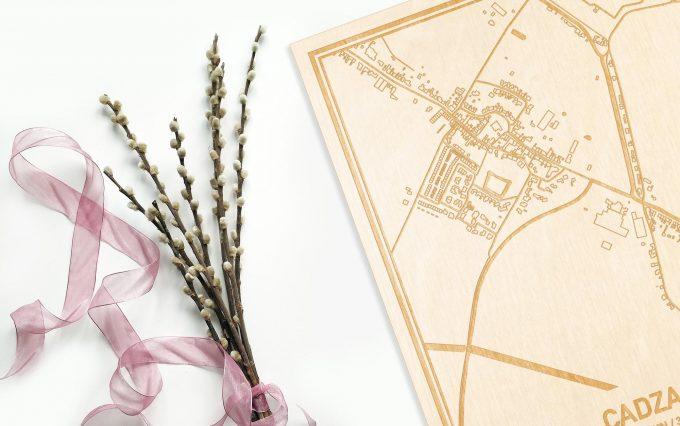 Hier ligt de houten plattegrond Cadzand naast een bloemetje als gepersonaliseerd cadeau voor haar.