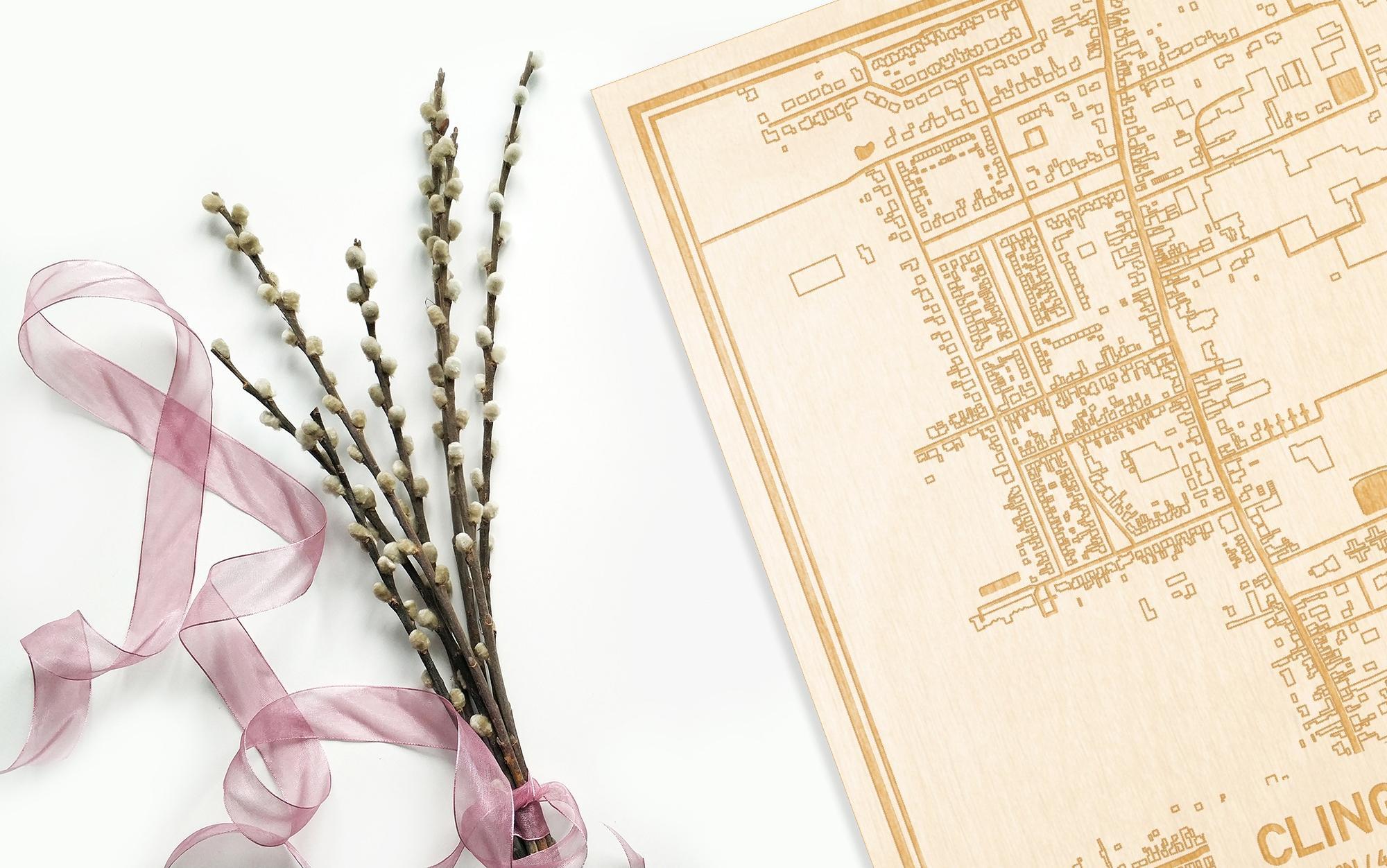 Hier ligt de houten plattegrond Clinge naast een bloemetje als gepersonaliseerd cadeau voor haar.
