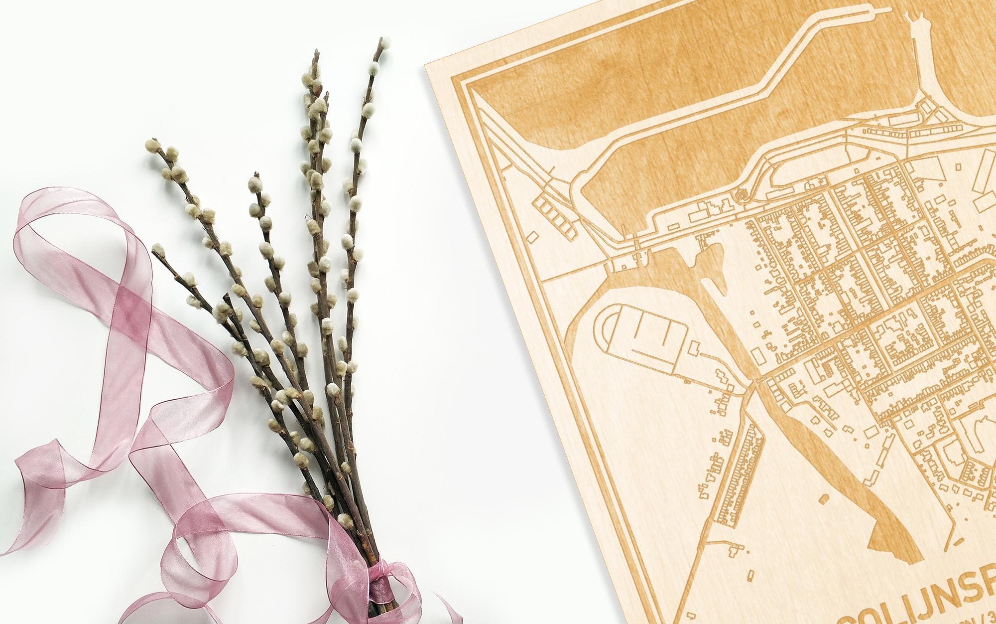 Hier ligt de houten plattegrond Colijnsplaat naast een bloemetje als gepersonaliseerd cadeau voor haar.