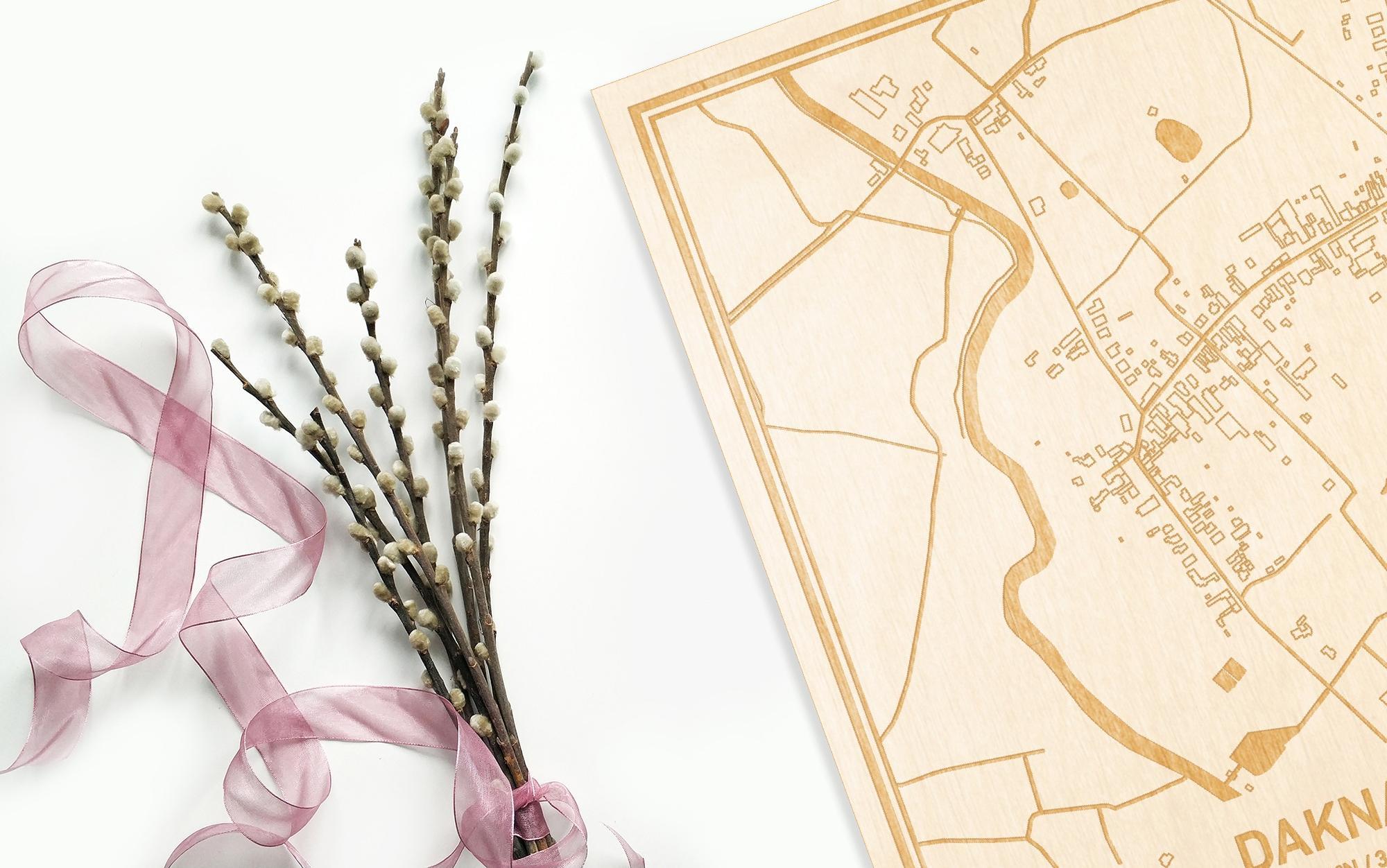 Hier ligt de houten plattegrond Daknam naast een bloemetje als gepersonaliseerd cadeau voor haar.