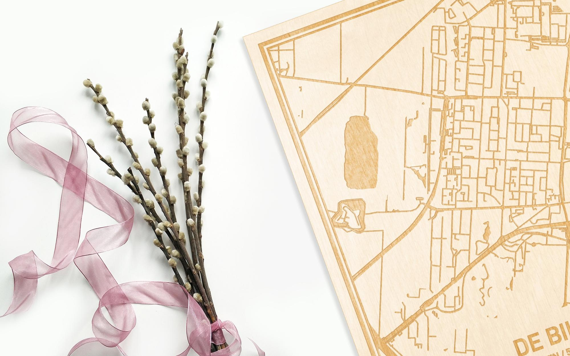 Hier ligt de houten plattegrond De Bilt naast een bloemetje als gepersonaliseerd cadeau voor haar.