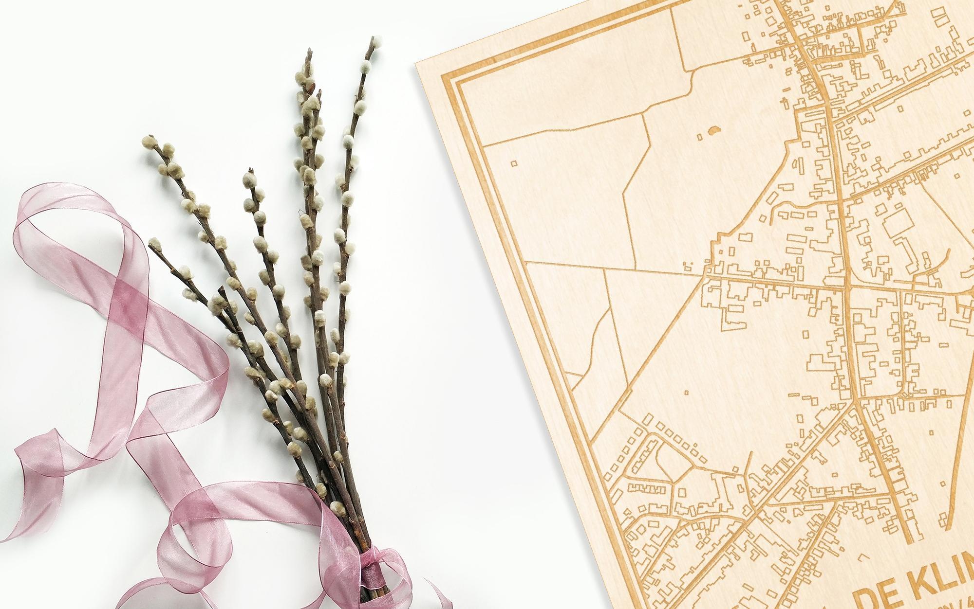 Hier ligt de houten plattegrond De Klinge naast een bloemetje als gepersonaliseerd cadeau voor haar.