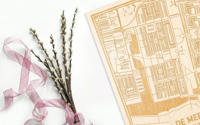 Hier ligt de houten plattegrond De Meern naast een bloemetje als gepersonaliseerd cadeau voor haar.
