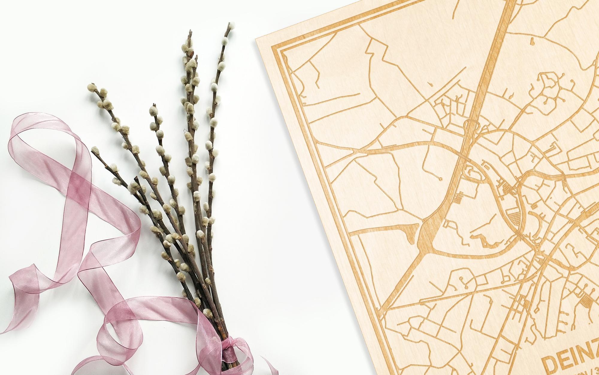 Hier ligt de houten plattegrond Deinze naast een bloemetje als gepersonaliseerd cadeau voor haar.