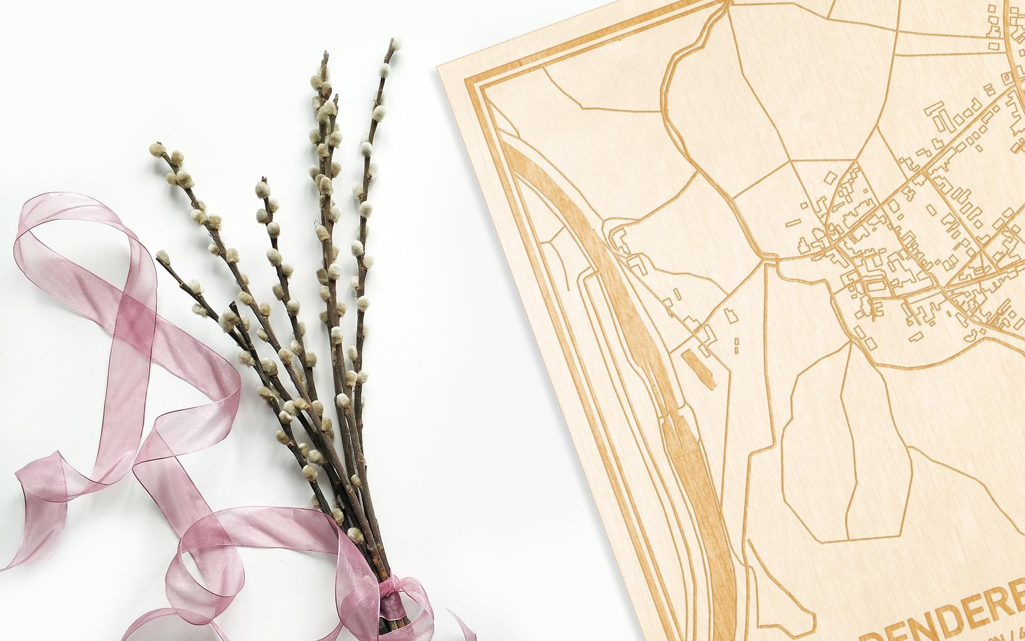 Hier ligt de houten plattegrond Denderbelle naast een bloemetje als gepersonaliseerd cadeau voor haar.