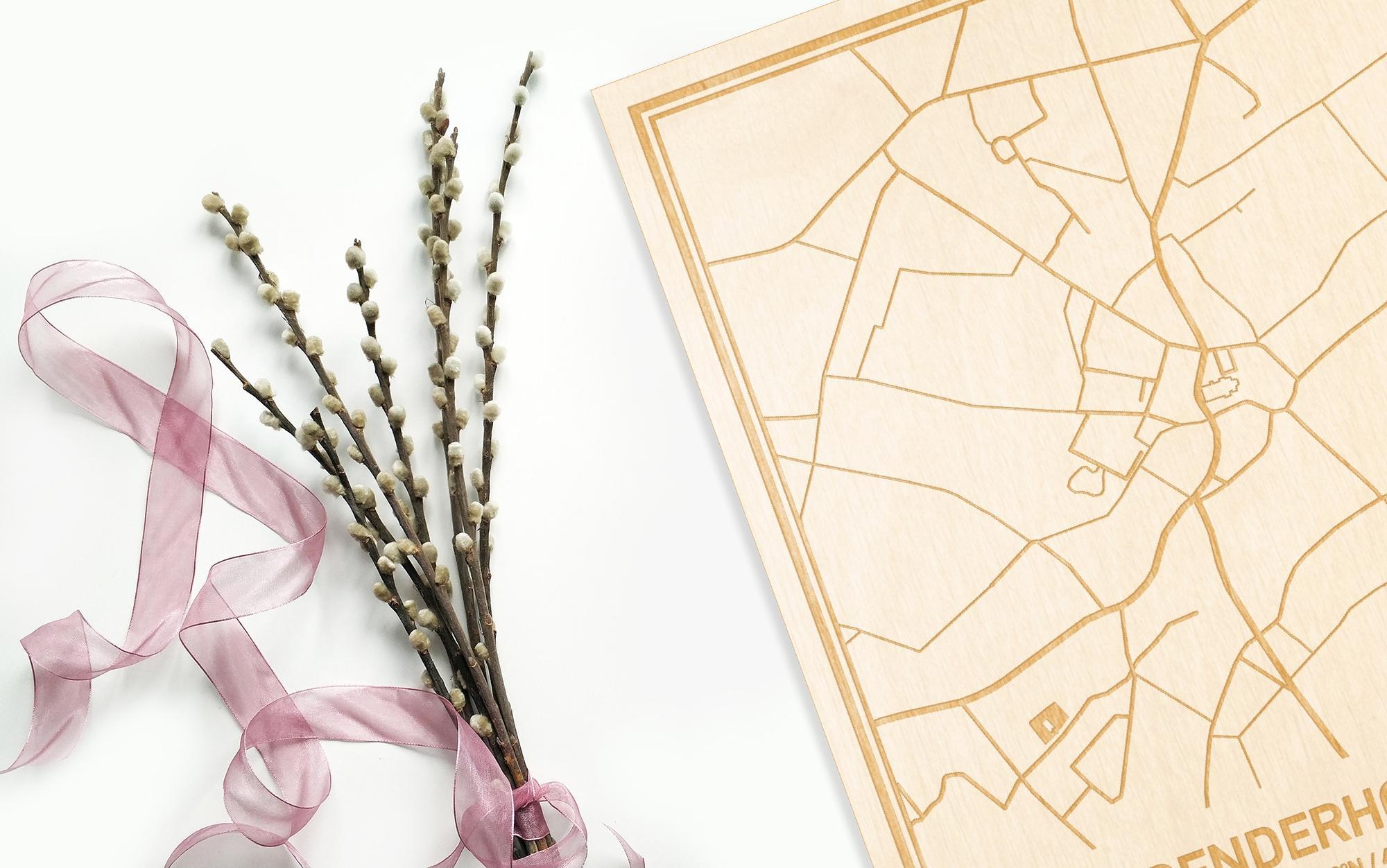 Hier ligt de houten plattegrond Denderhoutem naast een bloemetje als gepersonaliseerd cadeau voor haar.