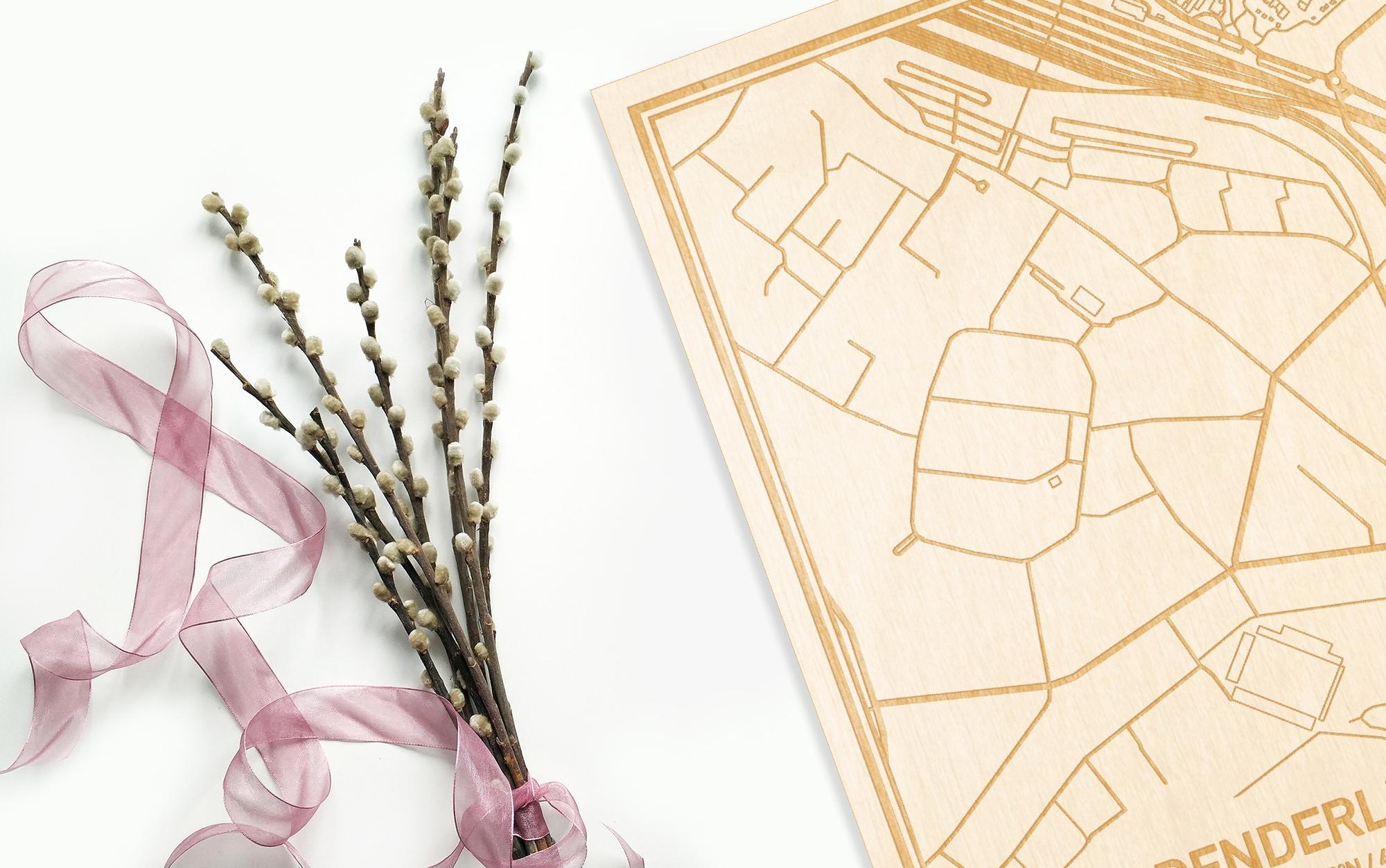 Hier ligt de houten plattegrond Denderleeuw naast een bloemetje als gepersonaliseerd cadeau voor haar.