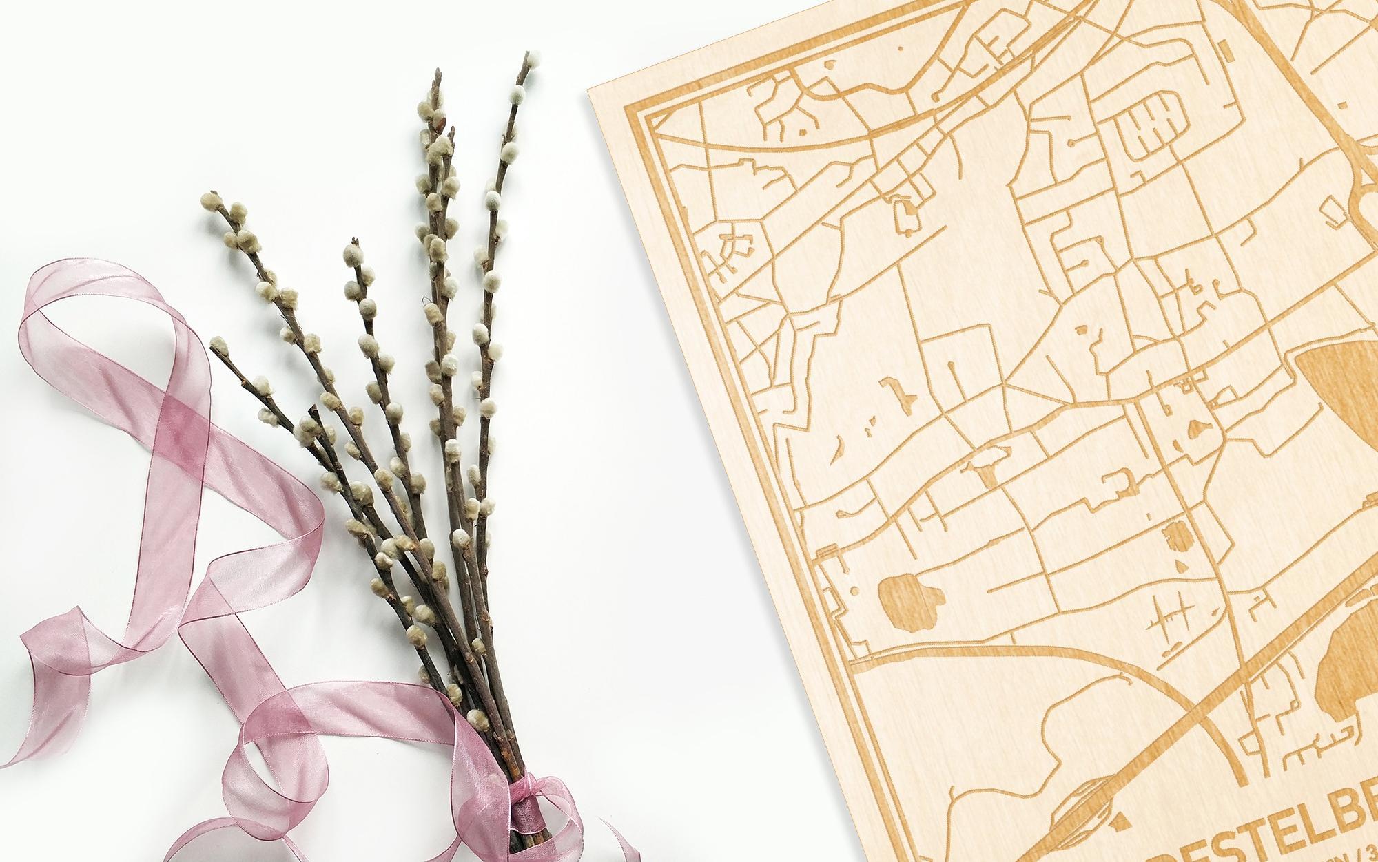 Hier ligt de houten plattegrond Destelbergen naast een bloemetje als gepersonaliseerd cadeau voor haar.