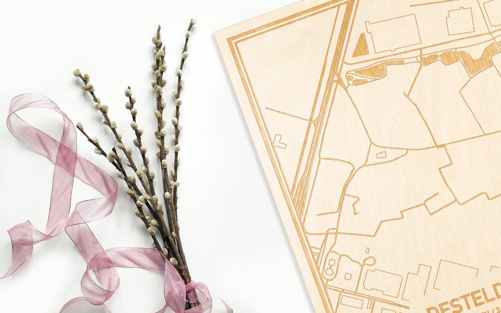 Hier ligt de houten plattegrond Desteldonk naast een bloemetje als gepersonaliseerd cadeau voor haar.