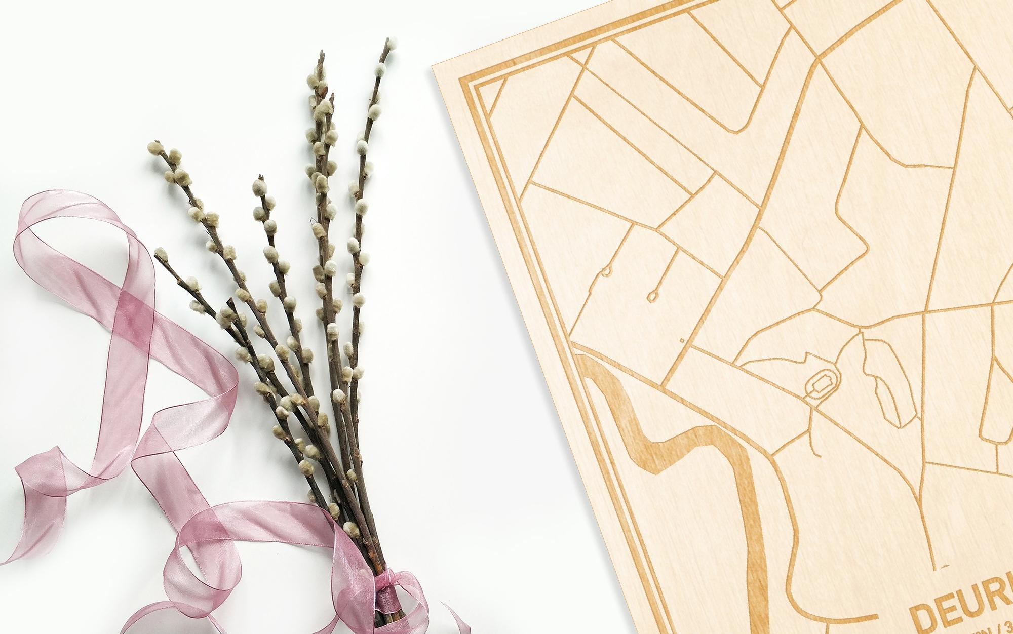 Hier ligt de houten plattegrond Deurle naast een bloemetje als gepersonaliseerd cadeau voor haar.