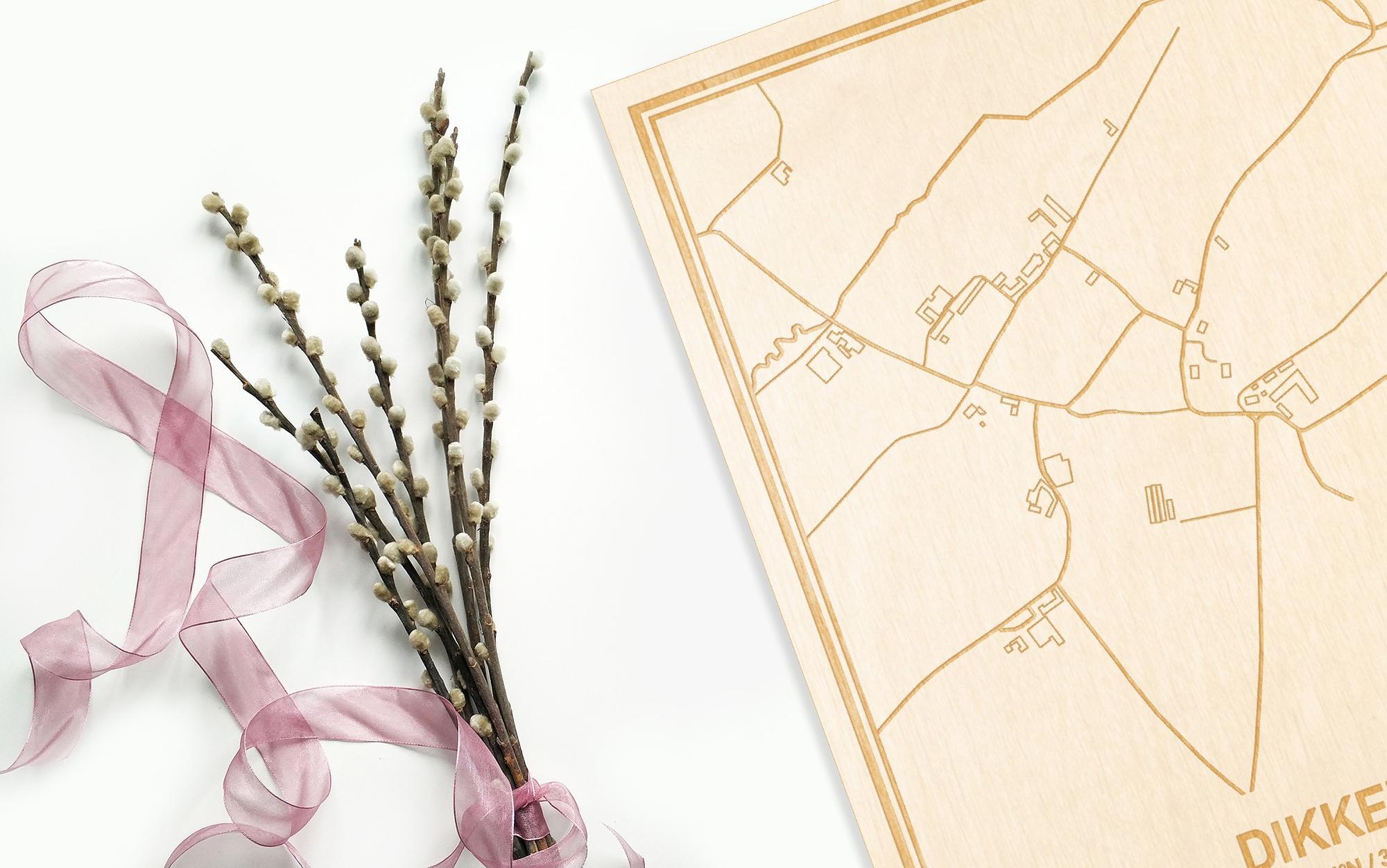 Hier ligt de houten plattegrond Dikkele naast een bloemetje als gepersonaliseerd cadeau voor haar.