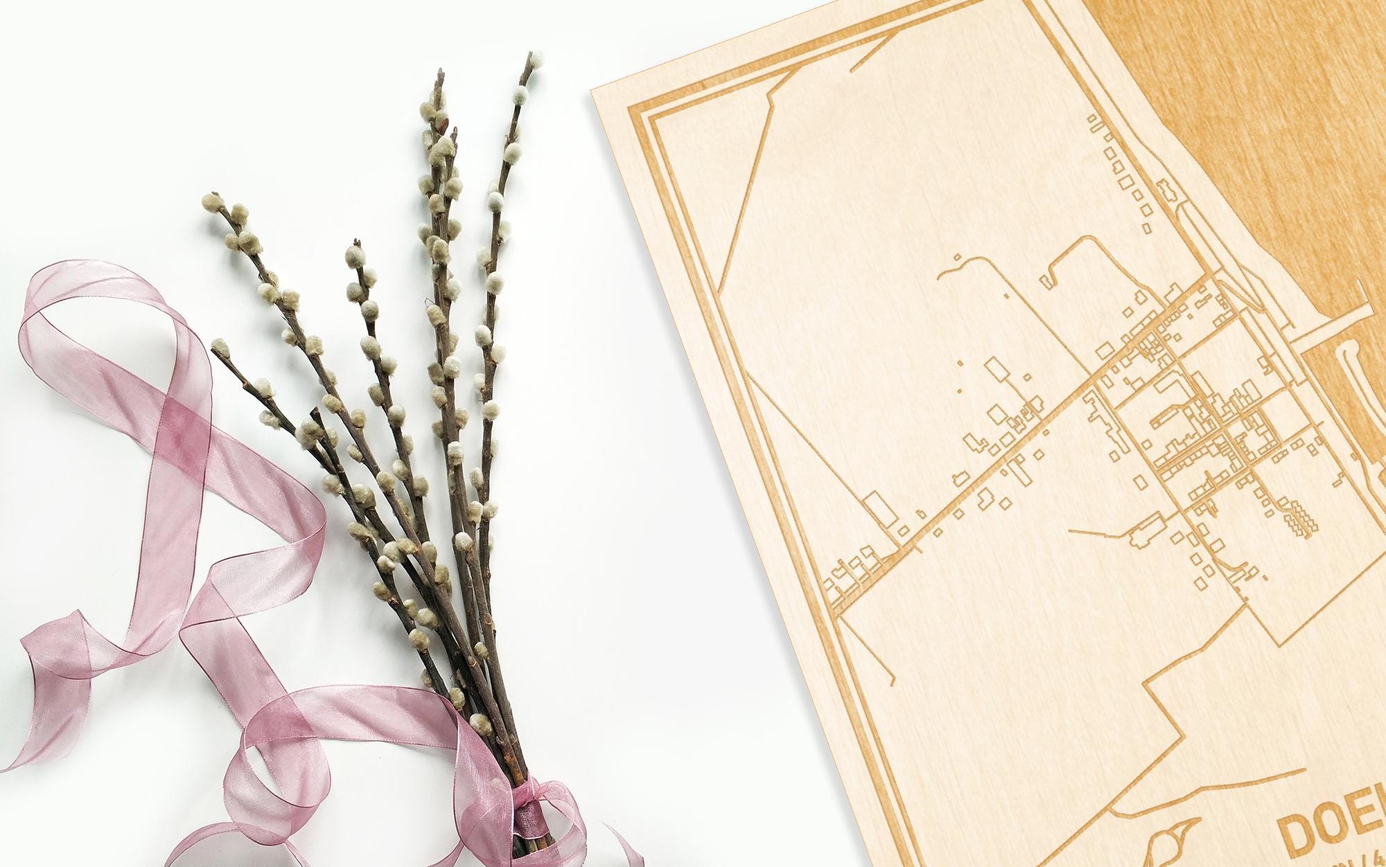 Hier ligt de houten plattegrond Doel naast een bloemetje als gepersonaliseerd cadeau voor haar.
