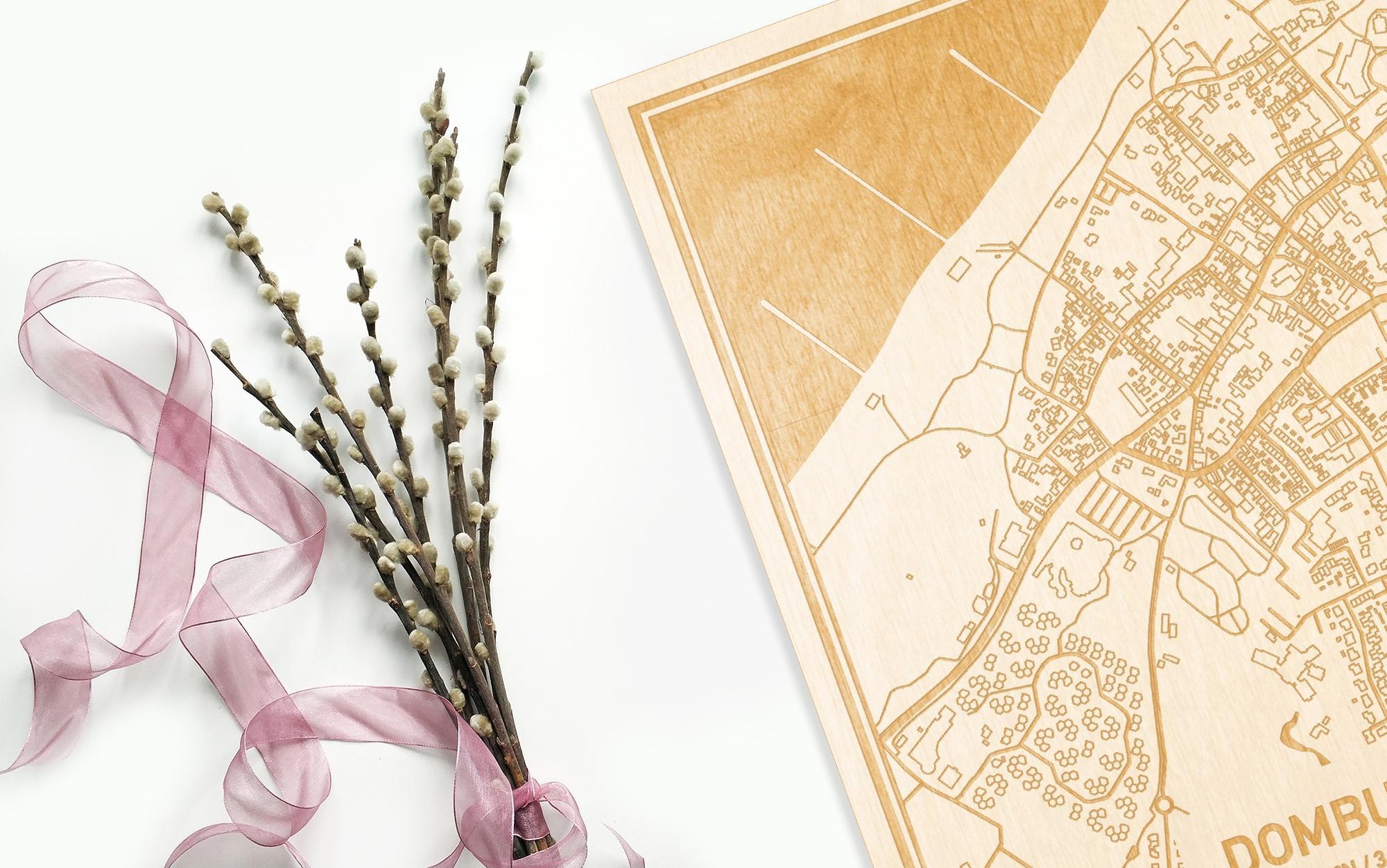 Hier ligt de houten plattegrond Domburg naast een bloemetje als gepersonaliseerd cadeau voor haar.