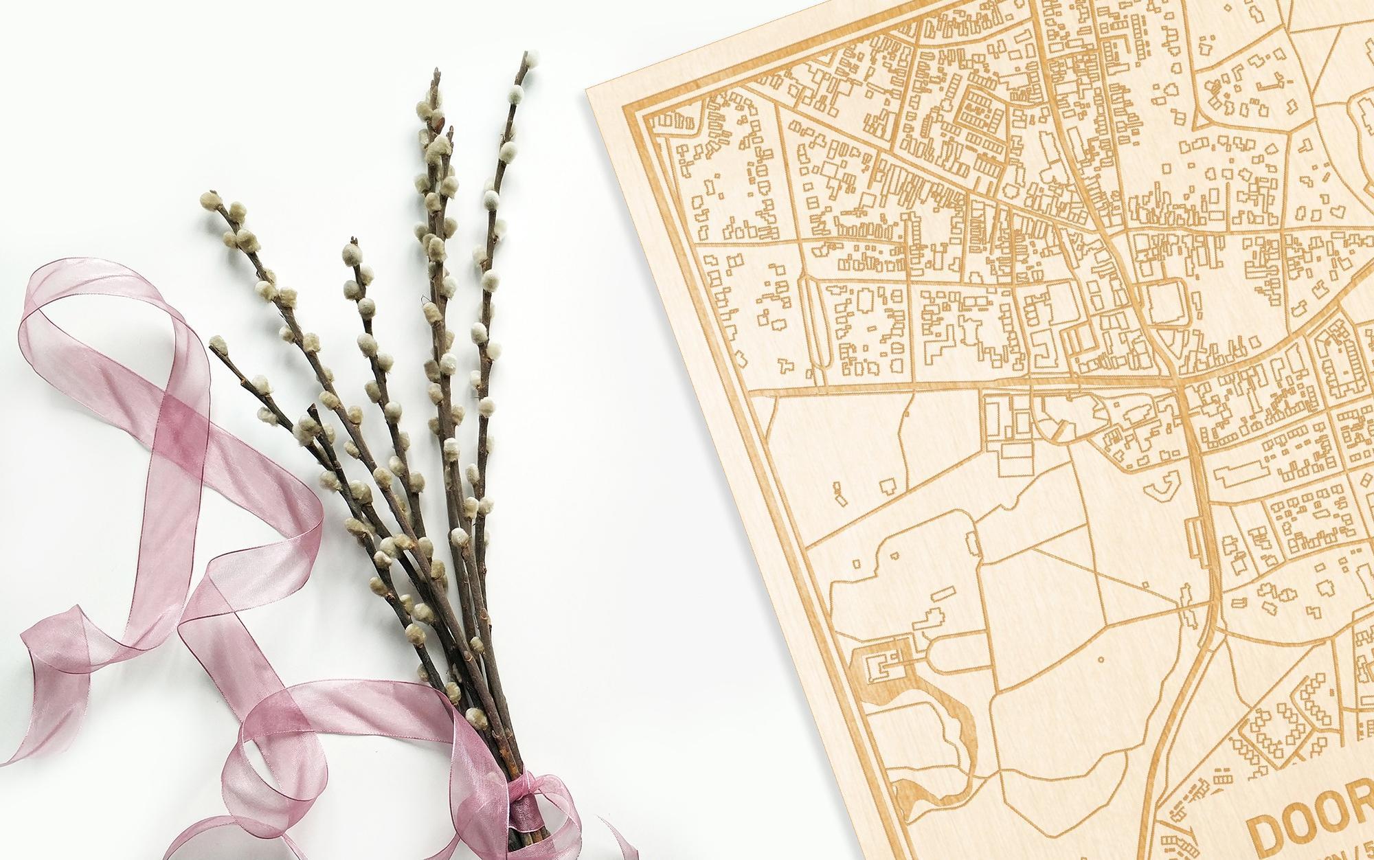 Hier ligt de houten plattegrond Doorn naast een bloemetje als gepersonaliseerd cadeau voor haar.