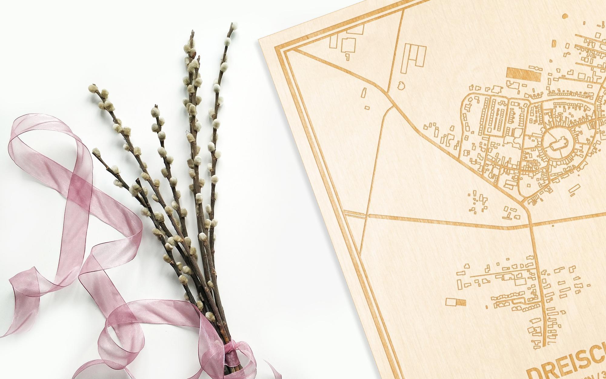 Hier ligt de houten plattegrond Dreischor naast een bloemetje als gepersonaliseerd cadeau voor haar.