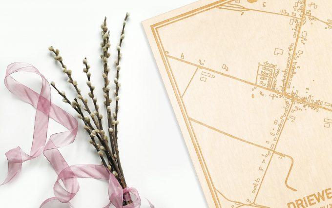 Hier ligt de houten plattegrond Driewegen naast een bloemetje als gepersonaliseerd cadeau voor haar.