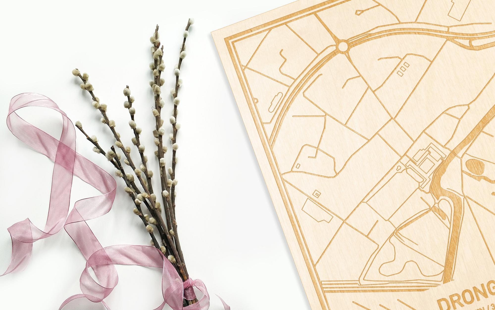 Hier ligt de houten plattegrond Drongen naast een bloemetje als gepersonaliseerd cadeau voor haar.