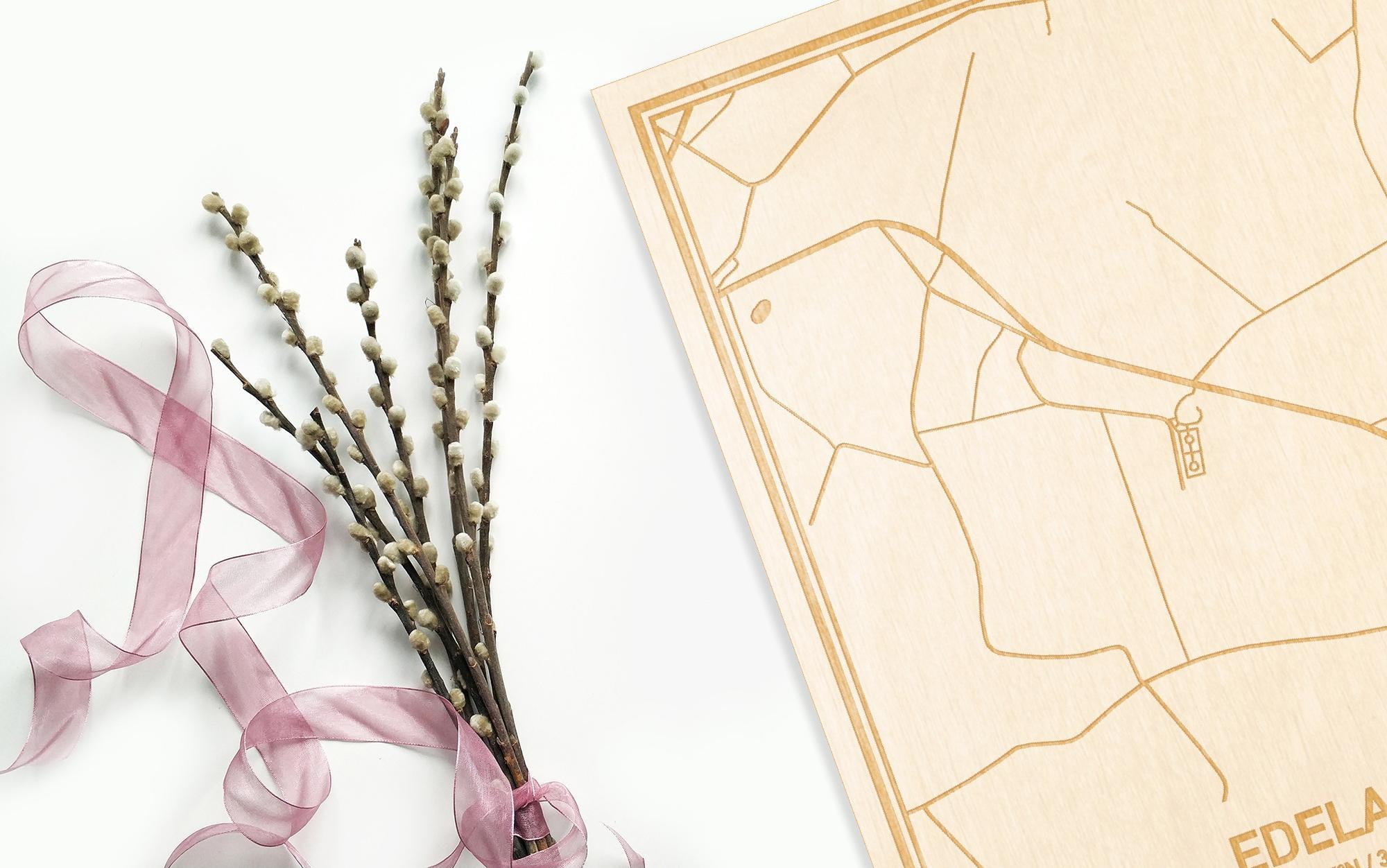 Hier ligt de houten plattegrond Edelare naast een bloemetje als gepersonaliseerd cadeau voor haar.