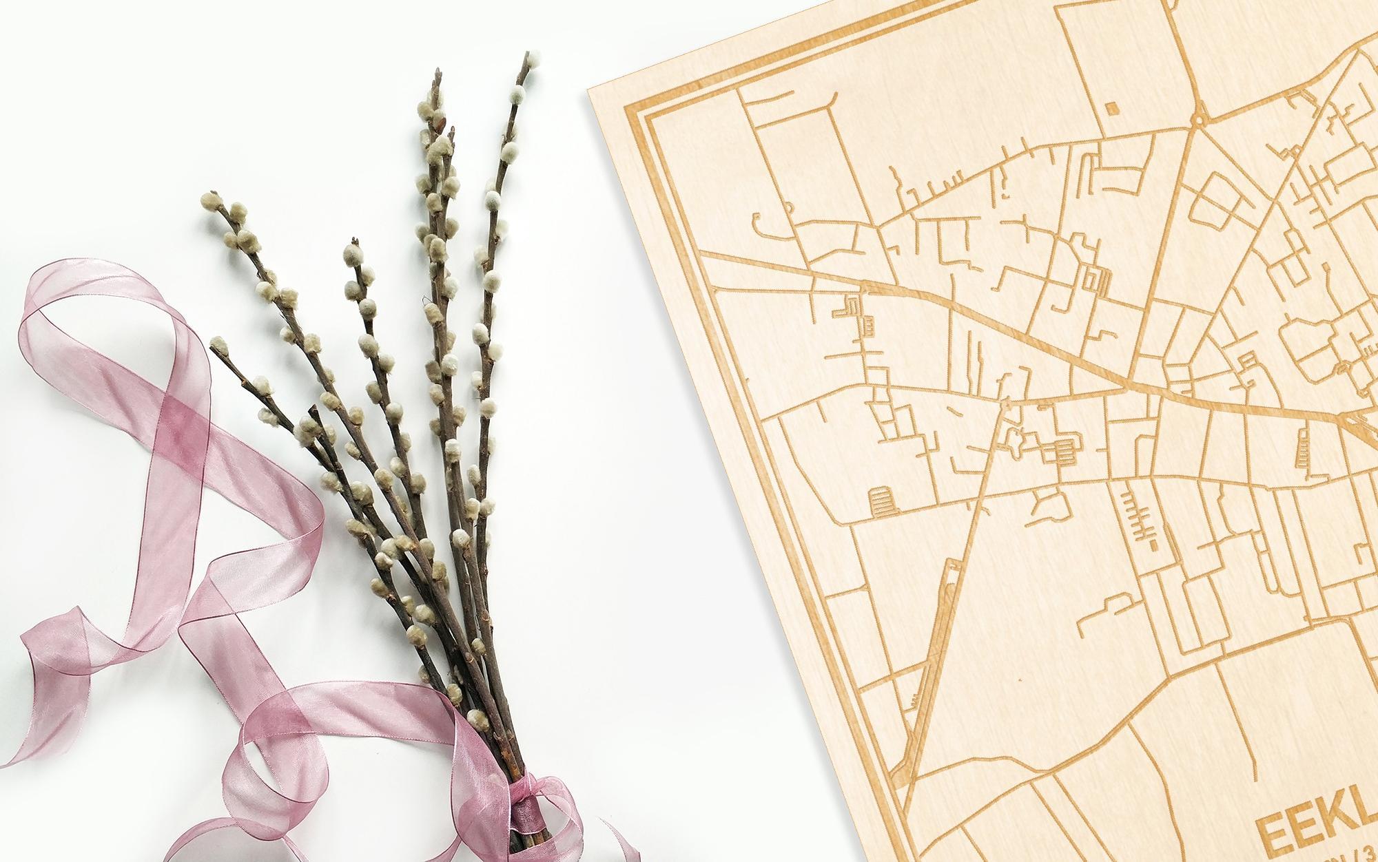 Hier ligt de houten plattegrond Eeklo naast een bloemetje als gepersonaliseerd cadeau voor haar.