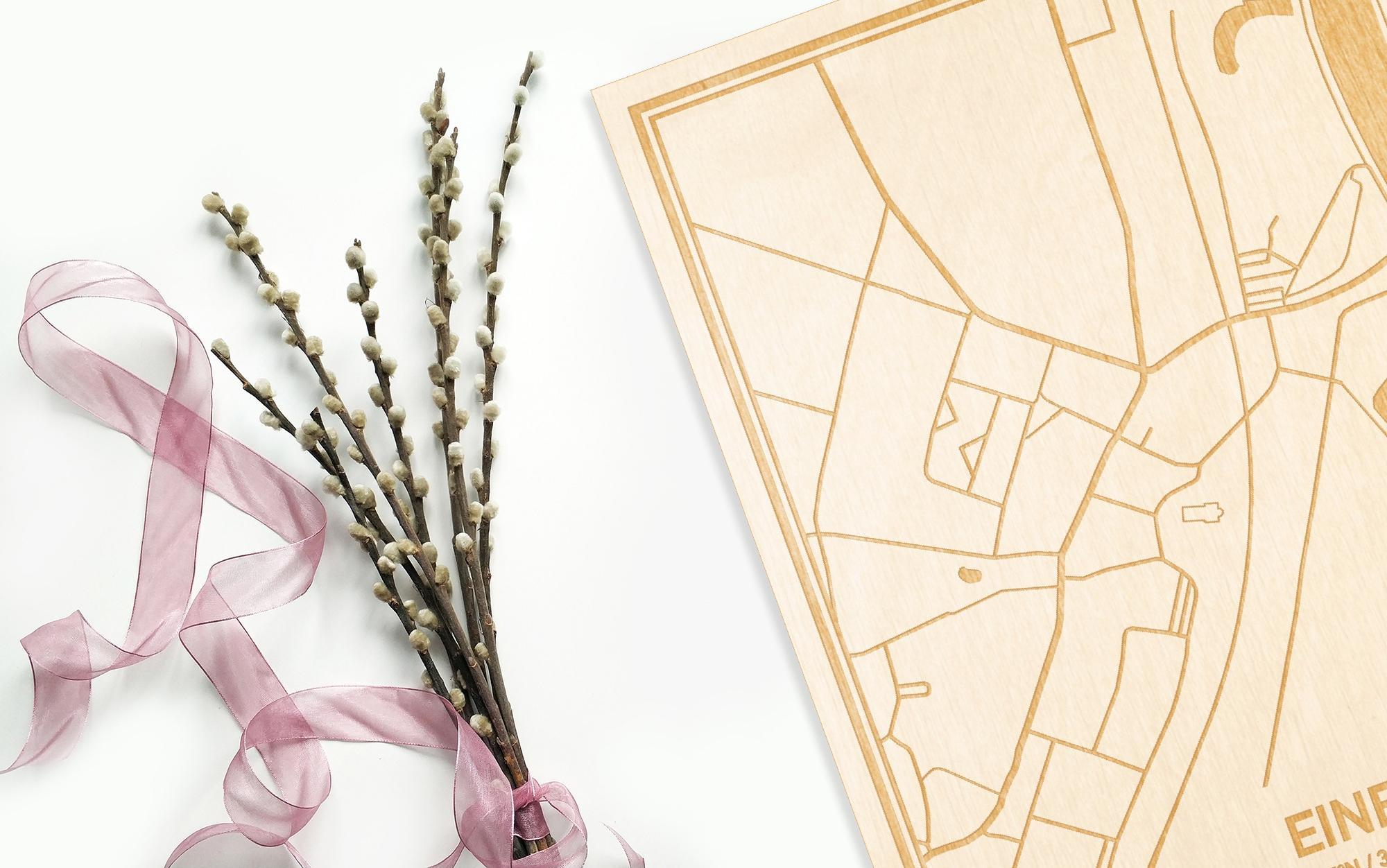 Hier ligt de houten plattegrond Eine naast een bloemetje als gepersonaliseerd cadeau voor haar.